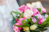 picture of broken heart flower  - A bride holding a bridal bouquet of ink purple and white roses with green leaves - JPG