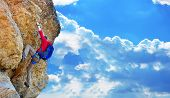 stock photo of cliffs  - rock climber with backpack climbing up a cliff - JPG