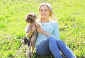 foto of yorkshire terrier  - Sunny portrait of happy young woman owner with yorkshire terrier dog sitting on the grass - JPG