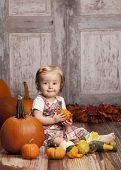 pic of gourds  - Adorable baby girl sitting next to pumpkins and gourds and other fall decor - JPG