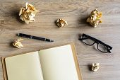 picture of stress-ball  - Crumpled paper balls with eye glasses and notebook on wood desk creative writing concept - JPG