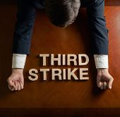 foto of striking  - Phrase Third Strike made of wooden block letters and devastated middle aged caucasian man in a black suit sitting at the table - JPG
