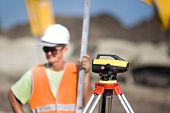picture of theodolite  - Surveying measuring equipment level theodolite on tripod at construction site with worker in background - JPG