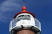 Closeup Of The Top Of A Lighthouse Against Blue Sky. poster