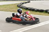 stock photo of karts  - Teenage boy sitting in go-kart at an outdoor track ** Note: Soft Focus at 100%, best at smaller sizes - JPG