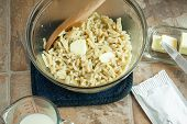 pic of elbows  - Elbow macaroni in a bowl with butter milk nearby and a dry cheese pack on the counter - JPG