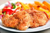 stock photo of potato chips  - Chicken schnitzels on a plate served with potato chips and green salad - JPG