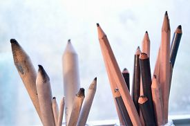 picture of charcoal  - Drawing and sketching tools. Graphite and charcoal pencils for fine art on the right and blending stumps or tortillons for blending pencil drawings to the left. Against a gray and white background. ** Note: Shallow depth of field - JPG