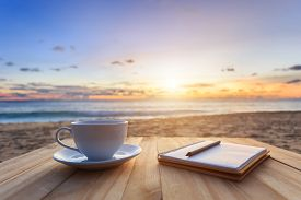 stock photo of morning sunrise  - Close up coffee cup on wood table at sunset or sunrise beach - JPG