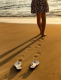 image of barefoot  - Woman waist down walking barefoot into Pacific Ocean during golden sunset - JPG