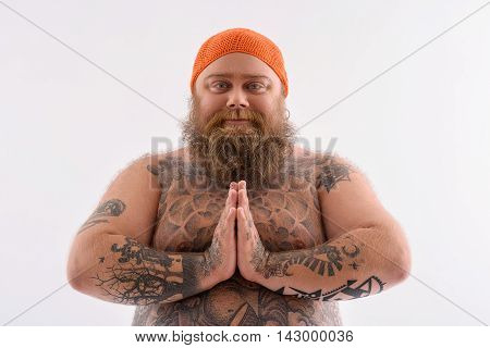 Peace makes me happy. Thick man with beard is looking at camera with joy. He is standing and joining hands. Isolated