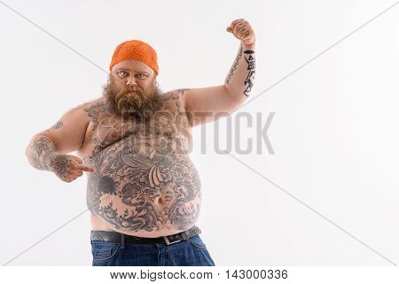 I am very strong. Fat bearded man is pointing finger at his big abdomen with proud. He is raising arm and showing muscle. Isolated and copy space in right side