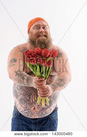 These flowers are for you. Joyful bearded fatty is holding tulips and stretching it to camera. Man smiling and looking forward with aspiration. Isolates