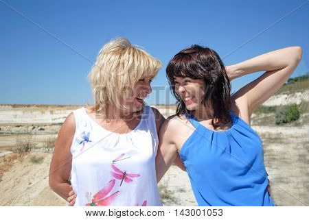 Two women of different ages standing and laughing. Warm family relationships. Blonde and brunette, mother and daughter, the succession of generations.