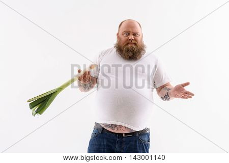 How can I eat it. Puzzled fat man is standing and holding leek. He is looking at camera with uncertainty. Isolated