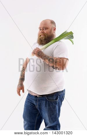 Cheerful fat man is carrying green vegetable. He is standing and looking at camera with joy. Isolated