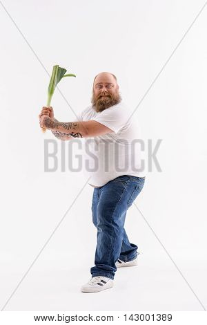 Fat bearded man is holding leek. He is standing in feedback position. Guy is looking at camera with preparation. Isolated