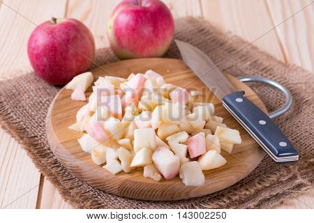 Cut apples on wooden cutting board with a knife