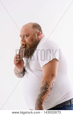 Hungry fat man is eating chocolate with desire. He is standing and looking forward with fear to be punished. Isolated on background