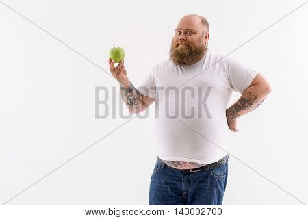 This is the best way to grow thin. Inspired fat man is holding apple. He is standing and looking at camera with joy. Isolated and copy space in left side