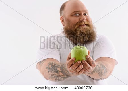 Fat man prefers healthy eating. He is holding apple and stretching it forward with joy. Man is standing and smiling