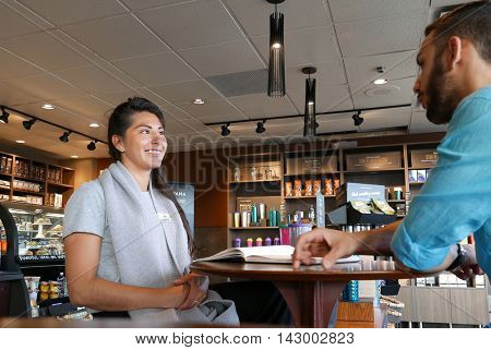 Coquitlam, BC, Canada - August 03, 2016 : One side of people drinking coffee and discussing business inside Starbucks store