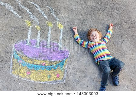 Happy little kid boy having fun with big birthday cake picture drawing with colorful chalks. Creative leisure for children outdoors in summer. Child celebrating birthday.