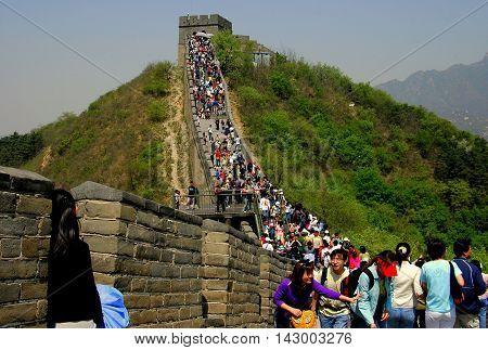 Badaling China - May 1. 2005: Throngs of visitors crowd the crenelated ramparts below a watctower at the Great Wall of China
