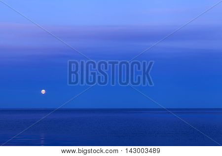 The sea in the Nordic summer night. Moon in the distance.