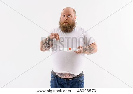 This is the last tomato. Thick bearded man is eating vegetable from plate. He is standing and looking at camera with shock. Isolated