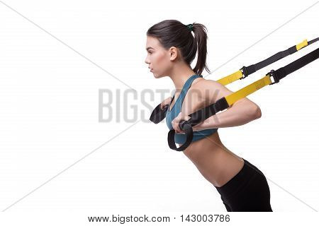 Upper body excercise concept. Beautiful woman exercising with suspension straps alone in studio. TRX concept isolated on white background.