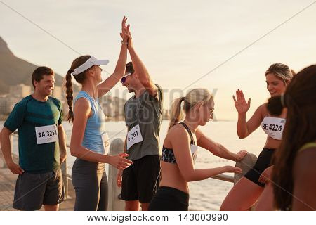Runners giving high five to each other after a training session. Group of athletes celebrating success after a race.