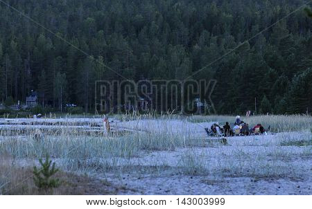 BALTIC SEA, SWEDEN ON JULY 22. View of a beach in nightfall on July 22, 2016 by the Baltic Sea, Sweden. Unidentified people on the beach, forest, hill in the background. Editorial use.