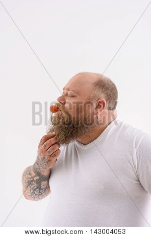 Eating is my love. Fat man is kissing small tomato. He standing and raising fork with vegetable to mouth. His eyes are closed with pleasure. Isolated