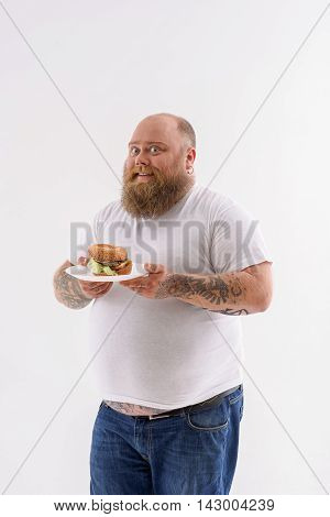 I like hamburger. Fat man is holding plate and smiling. He is standing and looking at camera with happiness. Isolated