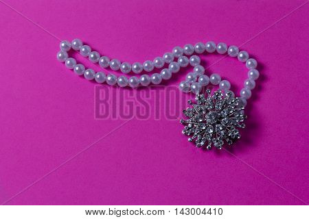 White beads on a pink background with a wonderful decoration