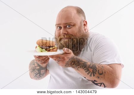 This is the best food ever. Cheerful fat man is holding plate of burger. He is standing and looking at camera with happiness. Isolated