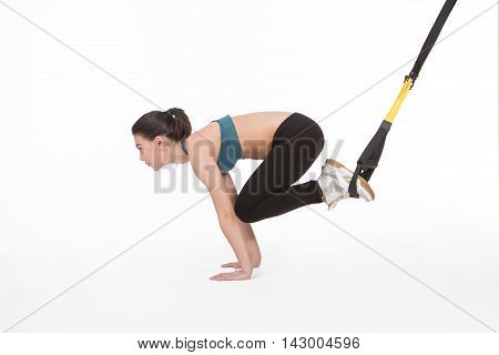 Core body excercise concept. Image of young attractive woman doing suspension training with fitness straps in studio. Beautiful lady training with suspension trainer sling isolated on white.
