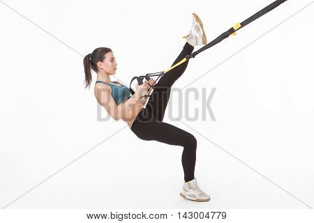 Core body excercise concept. Young lady exercising with suspension trainer sling isolated on white in studio. Beautiful woman practicing popular sport with suspension straps.