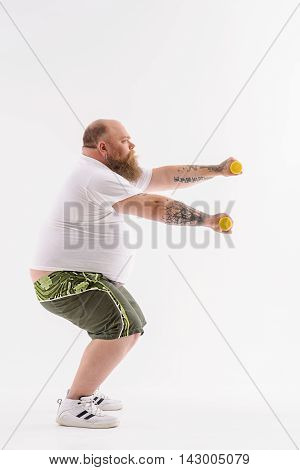 Motivated thick man is doing sit-ups and stretching arms forward. He is holding dumbbells and looking forward with seriousness. Isolated