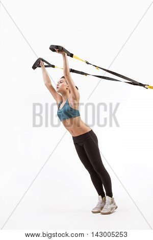 Upper body excercise concept on TRX. Beautiful young woman training with suspension trainer sling or suspension straps isolated on white background in studio.