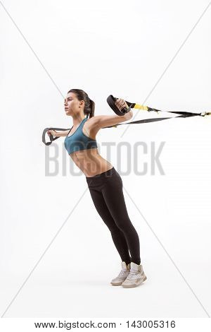 Low view of fitness trainer lady exercising on suspension trainer sling or suspension straps in studio. Upper body excercise on TRX isolated on white.