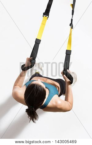 Upper body excercise on TRX isolated on white. Top view of fitness trainer lady exercising on suspension trainer sling or suspension straps in studio.
