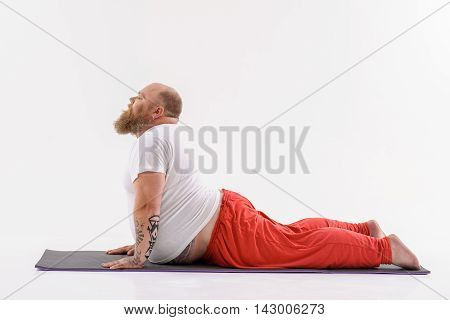 Thick man is exercising while meditating. He is lying on mat and stretching torso up. His eyes are closed with relaxation. Isolated