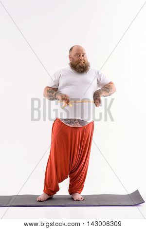 Fat man is measuring his body after exercising. He is holding tape over his belly. Man is standing and looking at camera with confidence. Isolated