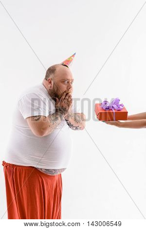 Thick man is celebrating his birthday. He is looking at gift box with shock. Man is standing with cone on head. Isolated