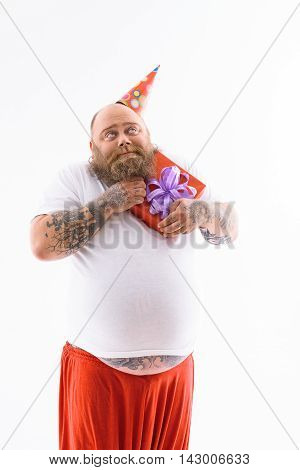 Happy fat man is embracing his birthday gift with love. He is standing and looking up dreamingly. Isolated