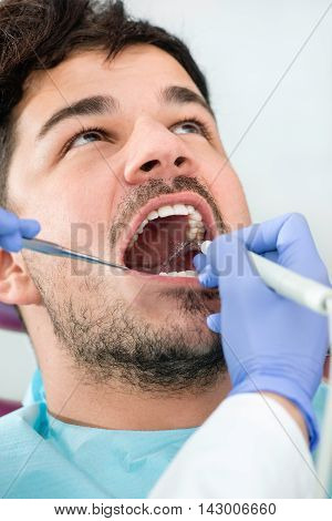 Dental plaque removal at dentist, vertical image