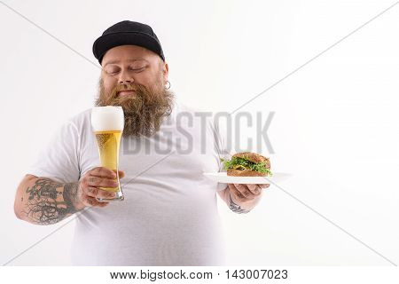Happy male fatso is enjoying unhealthy beer and hamburger. He is standing and smiling. Isolated and copy space in eight side