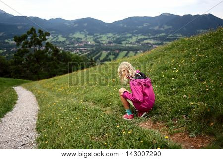 young girl is sitting in a flower field in nature